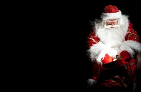 Kerstman zit op de kerst kamer en kijken in de zak Stockfoto