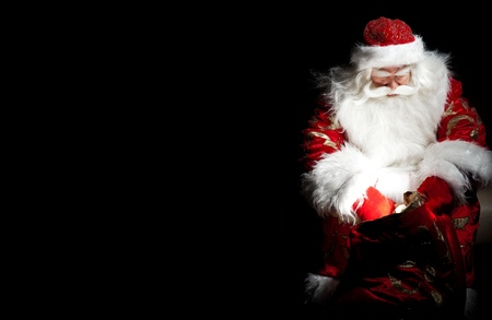christmas eve: Santa sitting at the Christmas room and looking into the sack Stock Photo