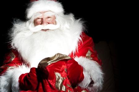 christmas santa: Santa sitting at the Christmas room and looking into the sack Stock Photo