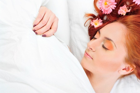 wellness sleepy: Closeup portrait of young beautiful caucasian woman with red hair lies on bed with fresh pure white linen. Flowers in her head. Stock Photo