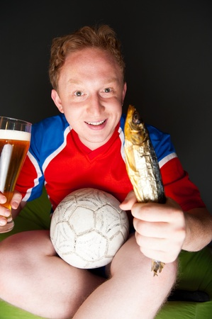 rooting: Closeup portrait of young man wearing sportswear fan of football team is watching tv and rooting for his favorite team  Sitting on beanbag alone at night drinking beer and eating fish  Stock Photo