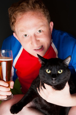 Portrait of young man holding a glass of beer and a big black cat and both looking at camera while watching tv translation of their favorite football team photo