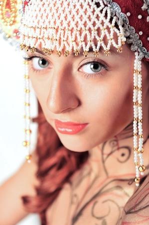 kokoshnik: Closeup portrait of pretty young woman with red hairs posing near wall smiling and wearing beautiful headwear - kokoshnik of russian traditional clothing.  Stock Photo