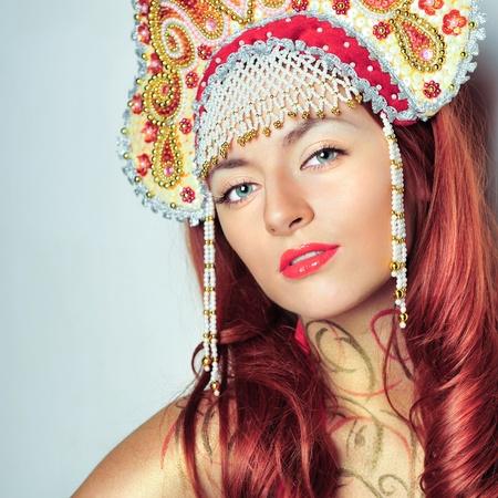 kokoshnik: Closeup portrait of pretty young woman with red hairs posing near wall smiling and wearing beautiful headwear - kokoshnik of russian traditional clothing. Copyspace.