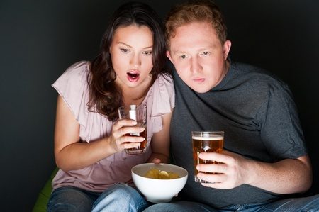 A couple watching a scary movie and it scared them so much that they are screaming. Stock Photo - 27136913