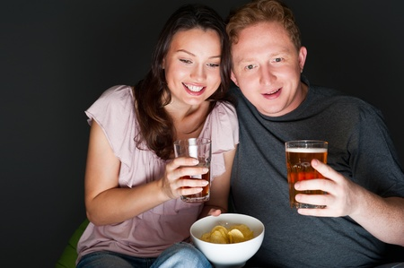 Happy couple sitting together watching something intresting on television drinking and eating - Grey background