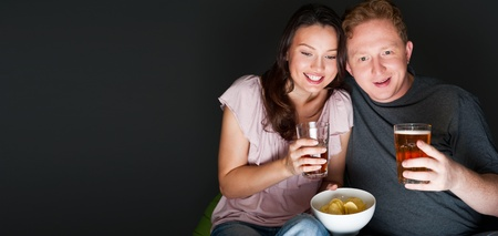 intresting: Happy couple sitting together watching something intresting on television drinking and eating - Grey background