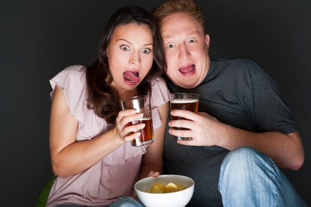 A couple watching a scary movie and it scared them so much that they are screaming. photo