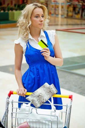 Photo of young joyful woman with shopping bags inside mall driving her trolley full of clothes, bags, shoes and other purchases photo