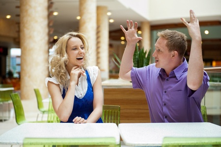body language: Young debating or talking couple inside mall sitting near the table