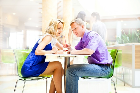 Closeup portrait of young cute couple at mall cafe.  photo