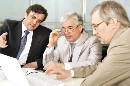 Retrato de tres hombres de negocios en la computadora. Fondo de la oficina.