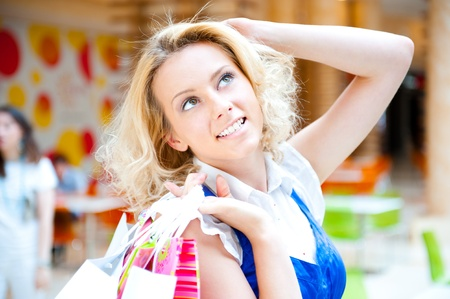 Happy shopping woman with bags inside modern mall daydreaming and smiling photo