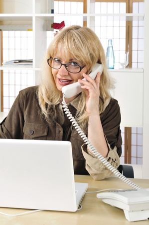 coporate: Portrait of a buisnesswoman on the telephone. Office background.