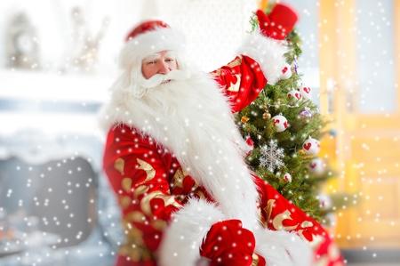 Santa sitting at the Christmas tree, near fireplace and looking at camera. Indoors. Magic snowy poster photo