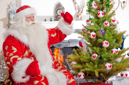 Santa sitting at the Christmas tree, near fireplace and looking at camera. Indoors photo
