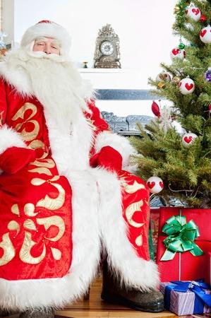 Santa sitting at the Christmas tree, fireplace and looking at camera photo