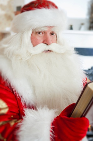 Santa sitting at the Christmas tree, near fireplace and reading a book. Indoors photo