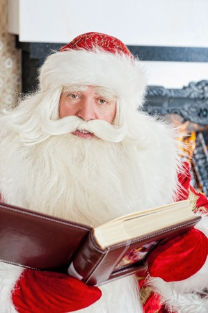 Santa sitting at the Christmas tree, fireplace and reading a book photo
