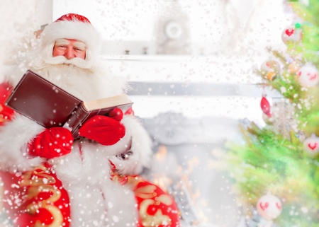 Santa sitting at the Christmas tree, near fireplace and reading a book. Indoors. Magic snowy poster photo