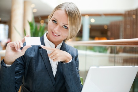 Portrait of a pretty businesswoman sitting at cafe with a laptop using wireless internet, showing business card to camera photo