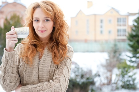 Portrait of young pretty red hair woman with cup of hot coffee or tea standing outdoor at winter background photo