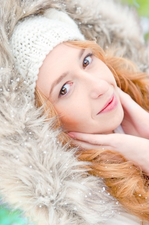 Portrait of pretty girl at winter background wearing warm clothes with fur photo