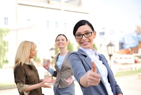 Business woman in a friendly environment of her colleagues stading outdoor and thumbs up with two of her partners at the back photo