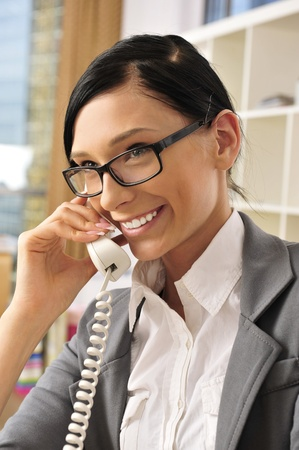 coporate: Portrait of a beautiful young businesswoman on the phone and happy. Office background. Stock Photo