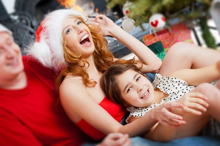 Young happy familye near a Christmas tree at home holding gift and warming from fireplace photo
