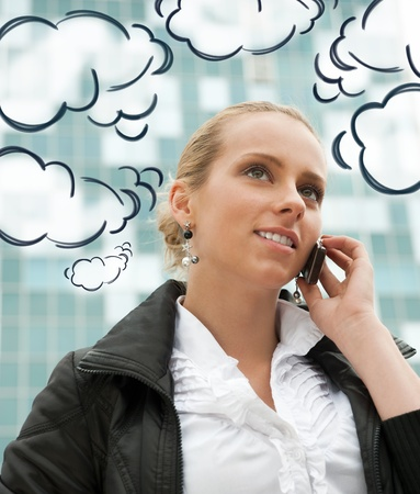 Portrait of pretty beautiful business woman on the phone with a modern building on background. Blank cloud balloons with her thoughts and replies around her Stock Photo