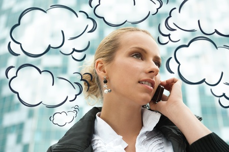 replies: Portrait of pretty beautiful business woman on the phone with a modern building on background. Blank cloud balloons with her thoughts and replies around her Stock Photo