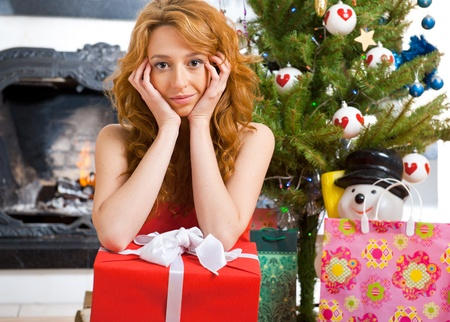 Christmas woman near a Christmas tree holding big gift box while sitting near Christmas Tree photo