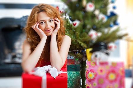 bawl: Christmas woman near a Christmas tree holding big gift box while sitting near Christmas Tree Stock Photo
