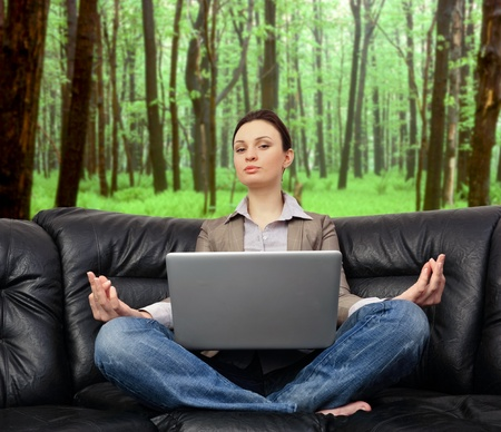 Portrait of young business woman sitting with a laptop on comfortable black couch and meditating on forest  photo