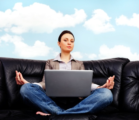 Portrait of young business woman sitting with a laptop on comfortable black couch and meditating on cyan sky  photo