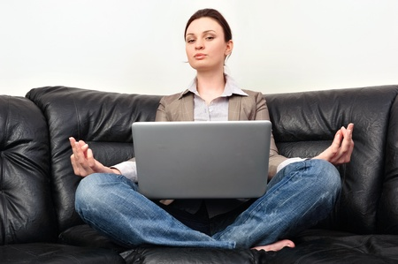 Portrait of young business woman sitting with a laptop on comfortable couch and meditating photo