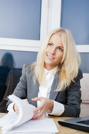 Beautiful business woman looking at papers she holding in her arms while working on computer at her office photo