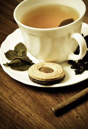 Cup of fresh tea with cigar and cookie on wooden table. Traditional english luxury breakfast. Retro style photo photo