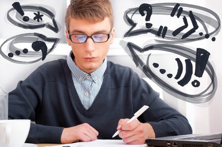 High school - Young male student write notes in classroom. Design balloons with his thoughts around his head Stock Photo