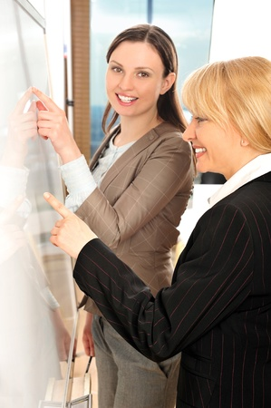 Closeup portrait of two young women discussing their business plans at white board in office environment photo