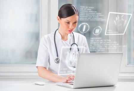 Vrij vrouwelijke geneeskunde arts die met moderne computer interface