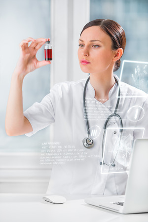 Portrait of pretty female laboratory assistant analyzing a blood sample at hospital near laptop with virtual display photo