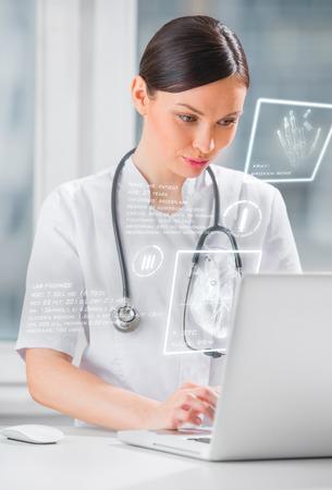 future medicine: Pretty female medicine doctor working with modern computer interface Stock Photo