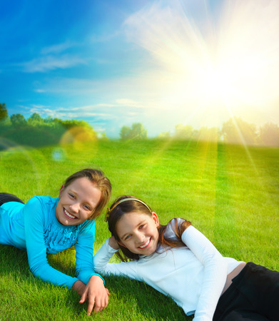 Two little sisters are resting on grass against idyllic landscape with sun and blue sky photo