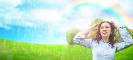 Young woman outdoors under rain against beautiful scenery. She is free and happy photo