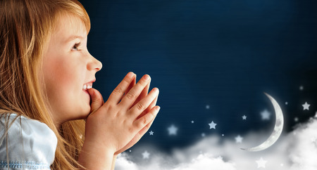 Portrait of little smiling praying girl in blue dress against dark fairy sky background with moon and stars Lots of copyspace