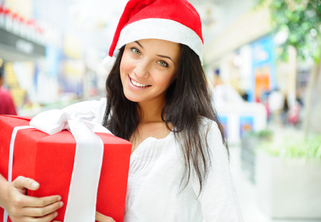 Portrait of young pretty woman wearing Santa Claus helper hat standing inside shopping mall smiling and holding christmas gift photo
