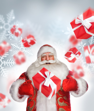 Laughing Santa Claus standing and doing magic. Gift boxes falling down around him photo