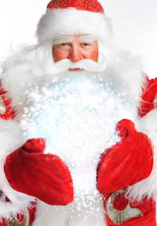 Traditional Santa Claus holding magic snowball Isolated on white Stock Photo